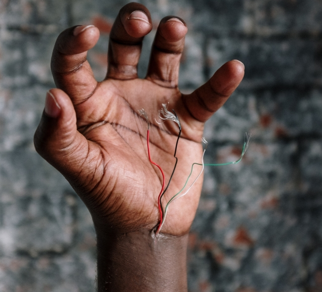 Hand with wires sticking out of it against an edgy gray brick background