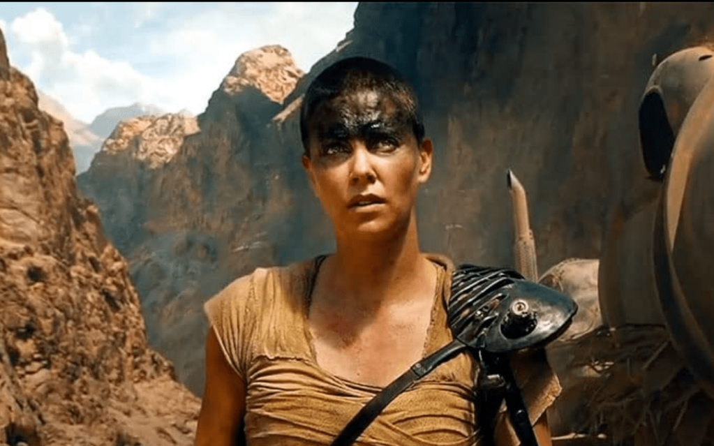 Charlize Theron as Furiosa in Mad Max: Fury Road--woman with short hair and black makeup over her eyes standing in a post-apocalyptic canyon