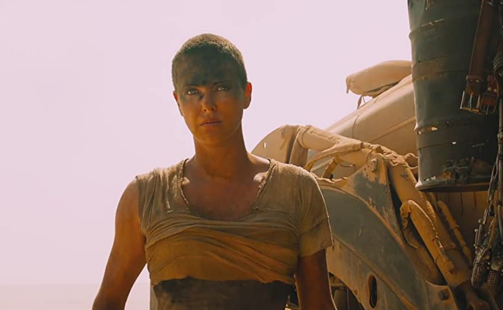 Medium close-up of a woman in rags and black makeup standing next to a rusty machine in the desert